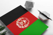 Fotografie Afghanistan flag on minimalist paper background. National invitation letter with stylish pen on stone. Communication concept.