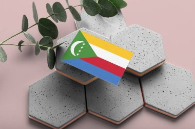 Comoros flag on hexagon stylish stones. Pink copy space background. Flat lay, top view minimal national concept.