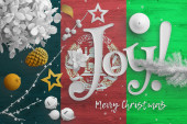 Fotografie Afghanistan flag on wooden table with joy text. Christmas and new year background, celebration national concept with white decor.