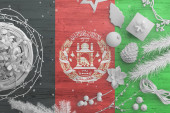 Fotografie Afghanistan flag on wooden table with snow objects. Christmas and new year background, celebration national concept with white decor.
