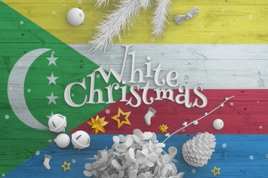 Comoros flag on wooden table with White Christmas text. Christmas and new year background, celebration national concept with white decor.
