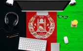 Fotografie Afghanistan flag background with headphone,computer keyboard and mouse on national office desk table.Top view with copy space.Flat Lay.