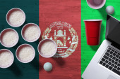 Fotografie Afghanistan flag concept with plastic beer pong cups and laptop on national wooden table, top view. Beer Pong game.