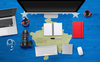 Kosovo flag background with headphone,camera, notebook and mouse on national office desk table.Top view with copy space.Flat Lay.
