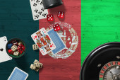 Fotografie Afghanistan casino theme. Aces in poker game, cards and chips on red table with national wooden flag background. Gambling and betting.