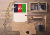 Afghanistan invitation, celebration letter concept. Flag with craft paper and envelope. Retro theme with divide, ink, wooden pen objects.