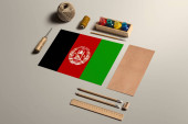 Afghanistan calligraphy concept, accessories and tools for beautiful handwriting, pencils, pens, ink, brush, craft paper and cardboard crafting on wooden table.