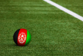 Afghanistan flag on ball at soccer field background. National football theme on green grass. Sports competition concept.