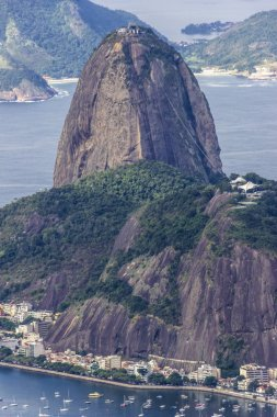 Views from Christ The Redeem mountain over Sugar Loaf, Rio do Janeiro city, suburbs and favelas, amazing views over the bays, islands, beach and the city skyline from the top on a cloudy day, Brazil