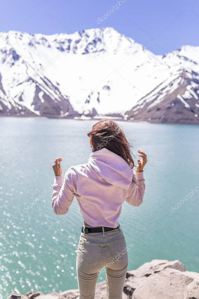 Girl looking at the amazing mountain view. with messy windy hair Turquoise waters of