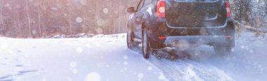 Car tires on winter road covered with snow. Snowy landscape with a vehicle winter snow background