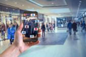 Chytrý telefon online nakupování v ruce člověka. Obchodní centrum v pozadí. Koupit oblečení boty s e commerce webové stránky