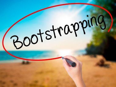Women Hand writing Bootstrapping with black marker on visual screen. Isolated on beach. Business, technology, internet concept. Stock Photo