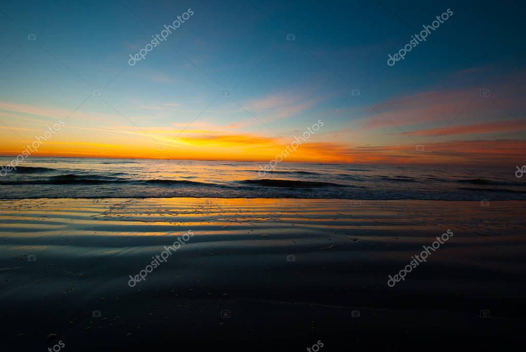 Photogrpah of a sunrise before the sun crests the horizon of a Saint Simons Island Beach.