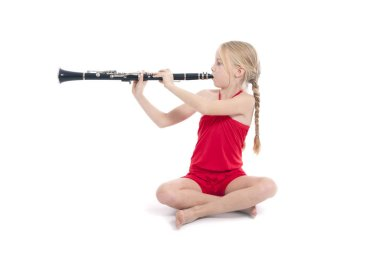 young sitting girl in red playing clarinet against white background