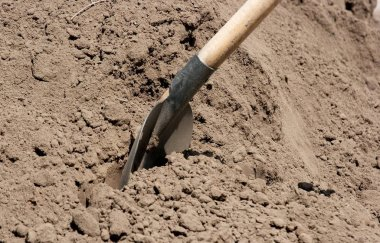 Shovel digging into a pike of soil