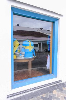 blue and yellow t-shirts in a blue colored shop window display