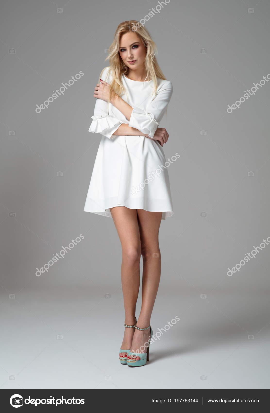 007272f06 Beautiful blond woman wear white dress and posing in studio– stock image