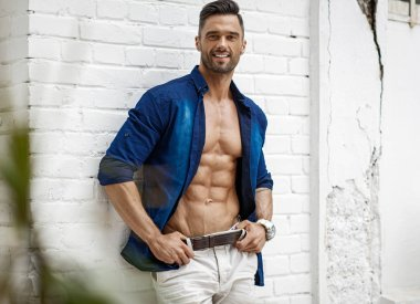 Sexy smiling male model posing outdoor in blue shirt with six pack