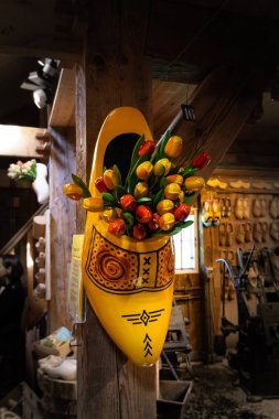 Beautiful colorful bouquets of wooden tulips in the wooden shoe. Decoration of a Dutch souvenir shop in Zaanse Schans, Netherlands, Europe