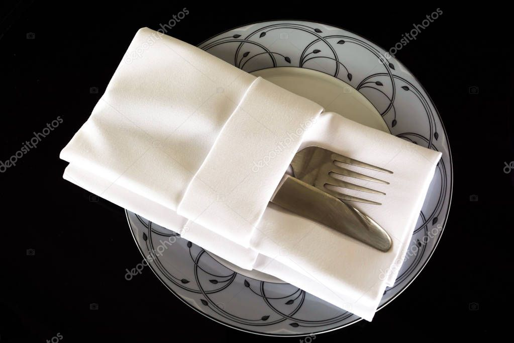FORK AND KNIFE IN NAPKIN OF RESTAURANT SERVICE SET , ISOLATED IN BLACK BACKGROUND