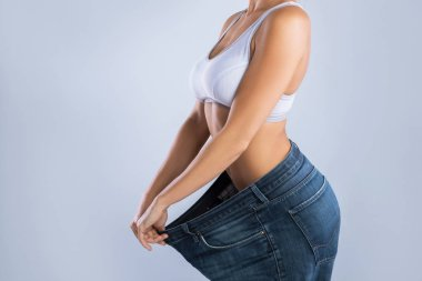 Woman after weight-loss trying her old jeans