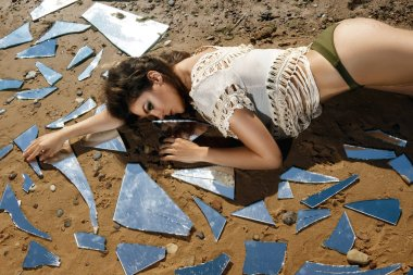 Beautiful young woman on the beach with a shards of mirror