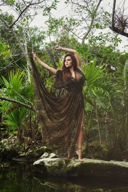 Sexy young woman wearing dress with wild print in tropical jungle