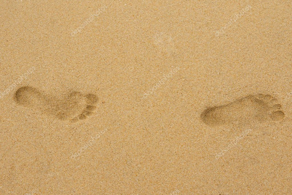 Close up view of two footprints on the sand