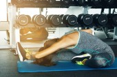 Photo Sporty young woman doing stretching exercise in the gym