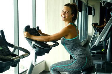 sporty young woman on stationary bike in the gym