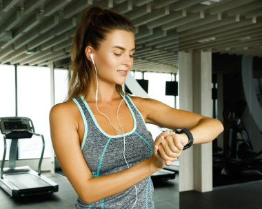 Woman using smart watch in the gym during her workout