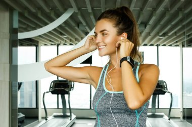 Sporty woman listening music during workout in gym