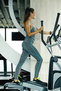 Sporty woman on elliptical trainer in the gym