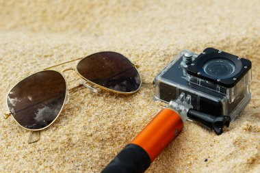 Sunglasses and action-cam on sandy beach
