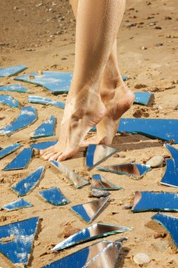Female legs and mirror shards on sand