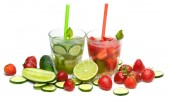 Refreshing drink with strawberries, limes and cucumbers on white background