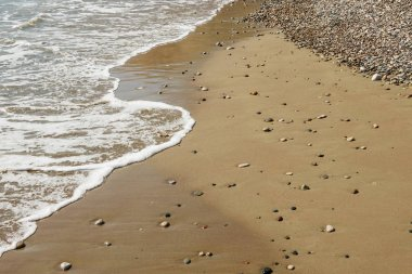 Pebble stones on sandy beach with sea wave