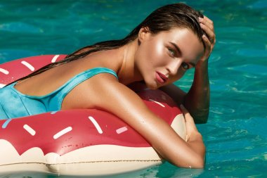 Beautiful young woman and inflatable swim ring in shape of a donut in pool