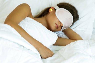 Woman is wearing eye mask and using earplugs for better sleeping