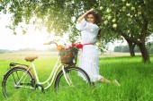 Fotografie Lovely woman with bicycle near apple tree in village garden