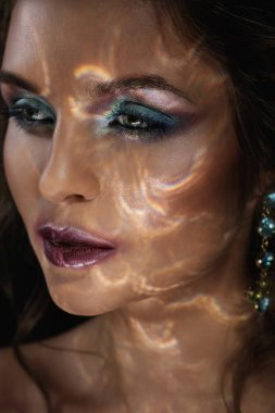 Beautiful woman in darkness with a light reflection on her face