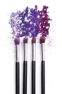 Crushed eyeshadows and make-up brushes on white background stock vector