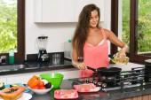 Fotografie glückliche Hausfrau beim Kochen in der Küche