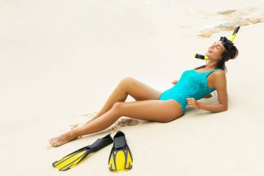Beautiful woman with mask and flippers for snorkeling on beach