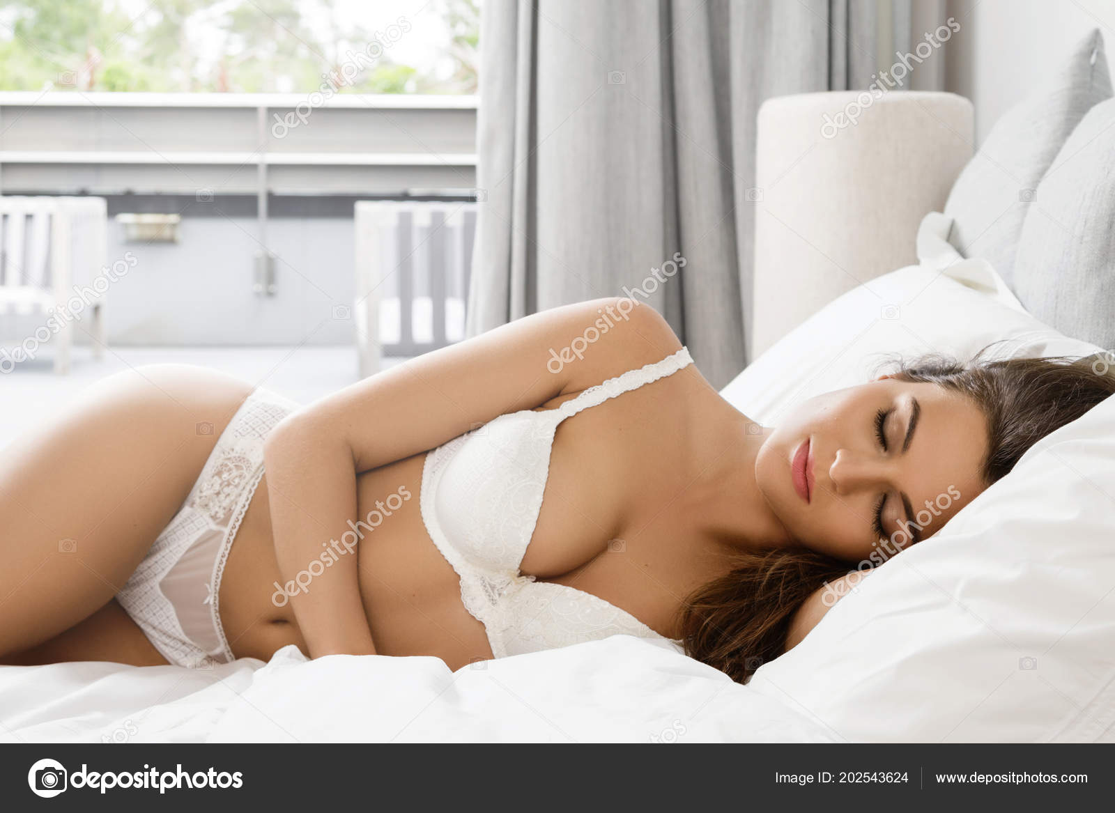 Beautiful sexy woman in white lingerie posing in bed– stock image 3bc3439c7