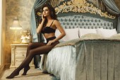 Photo Sexy young woman wearing a beautiful lingerie and a black tights in the luxury bedroom