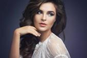 Fotografia Ritratto di giovane donna in vestito bianco con bello trucco e acconciatura