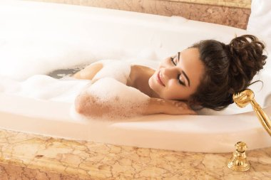 beautiful young woman taking bath with foam in luxury apartments