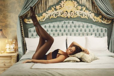 Sexy young woman wearing a beautiful lingerie and a black tights in the luxury bedroom